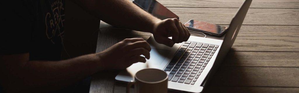 Manos del hombre navegando por el diccionario de comercio electrónico en el laptop
