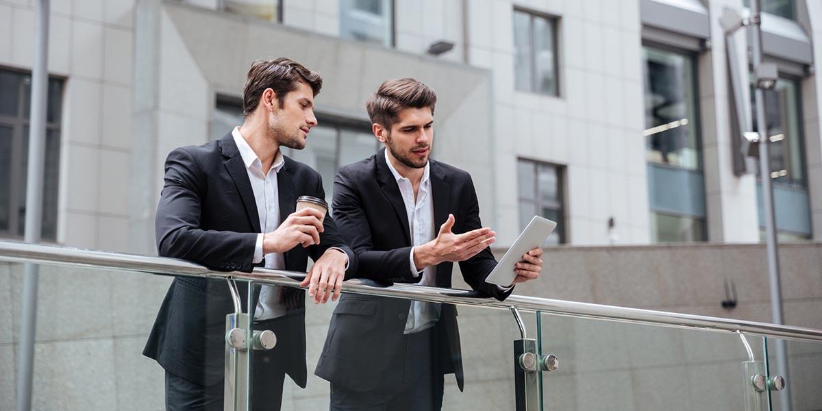 Dos hombres que consultan las ventajas en el tablet de la computación en la nube