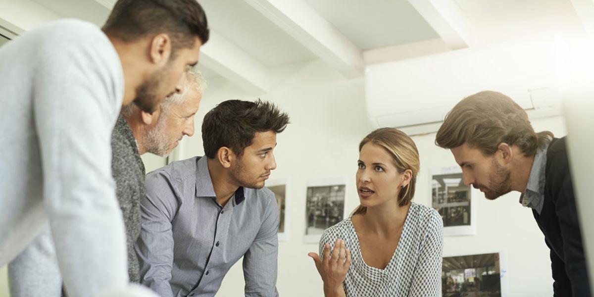 Reunión de trabajo de un equipo de alta performance con cuatro hombres escuchando a una mujer hablando
