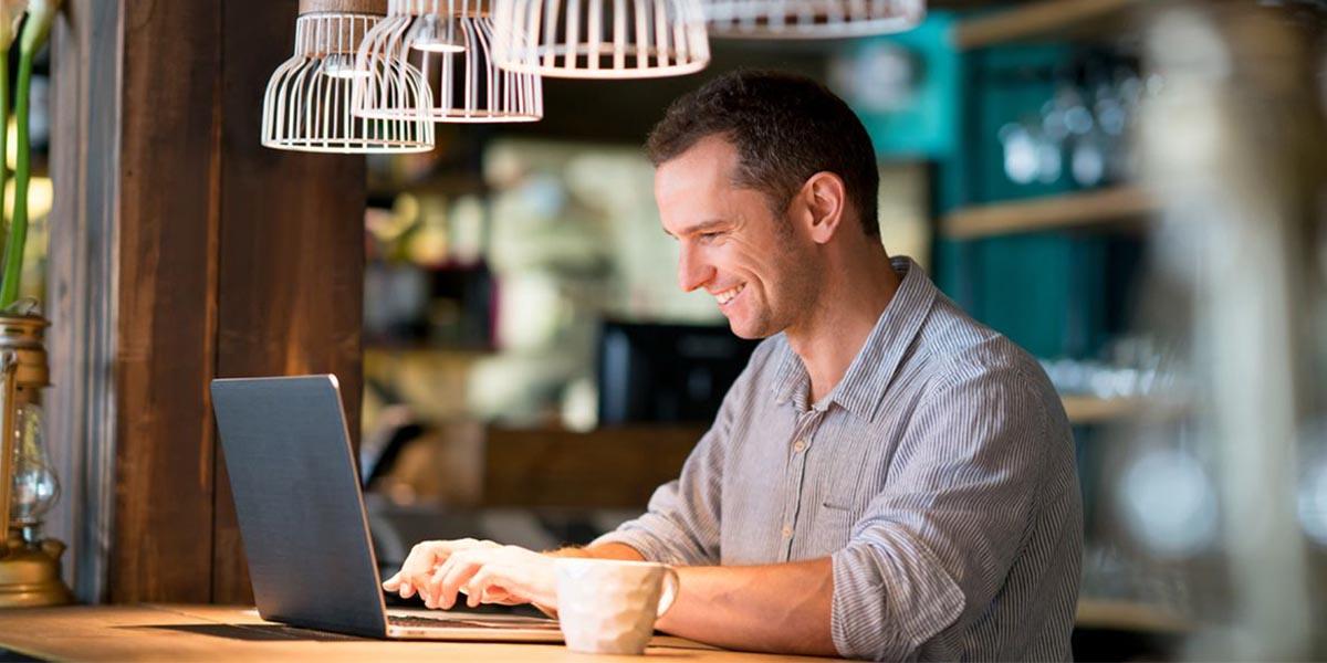 Hombre sentado en un escritorio escribiendo en el laptop sobre Facturación electrónica