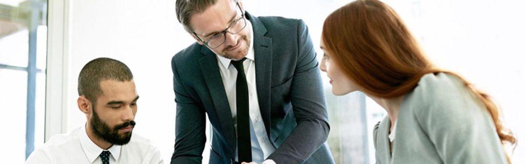 Un hombre y una mujer sentados mirando y escuchando al líder de una empresa a gestionar una empresa con un tablet