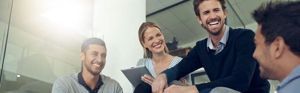 Reunión de negocios entre tres hombres y una mujer, todos sentados y la mujer sosteniendo una tableta con open banking