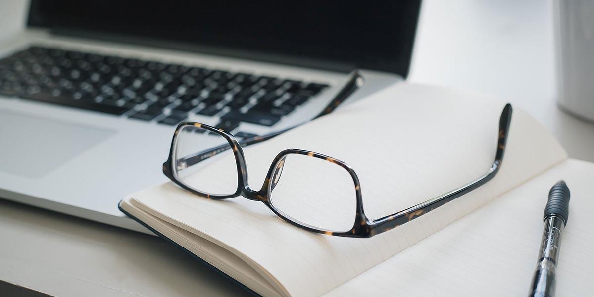 Gafas y un bolígrafo negro posado en una libreta vacía y un laptop desconectado listo para preparar el plan de negocios