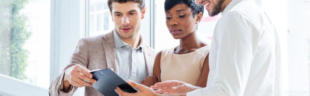 Dos hombres y una mujer que consultan en un tablet la estructura de un plan de negocios