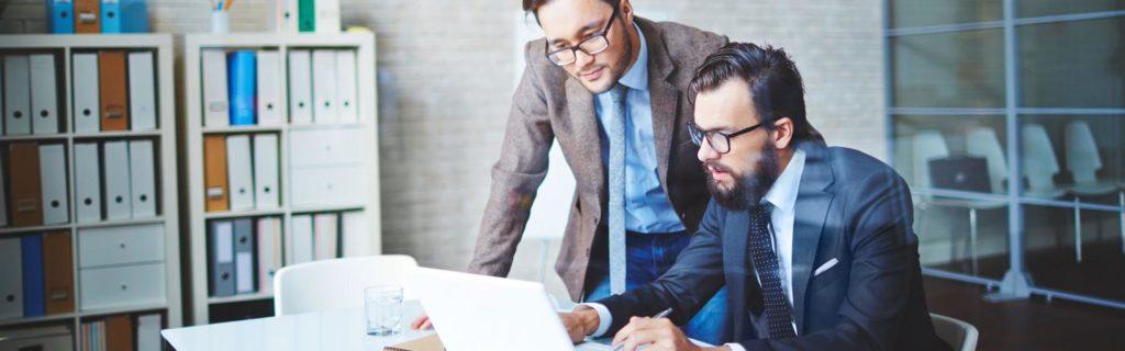 Dos gerentes masculinos que consultan mediciones en covid-19 en laptop