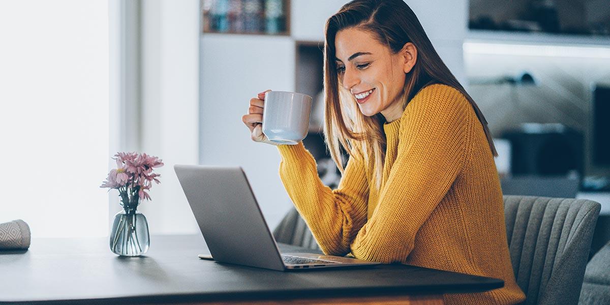 Mujer sosteniendo una taza de café mientras mira el portátil y hace teletrabajo