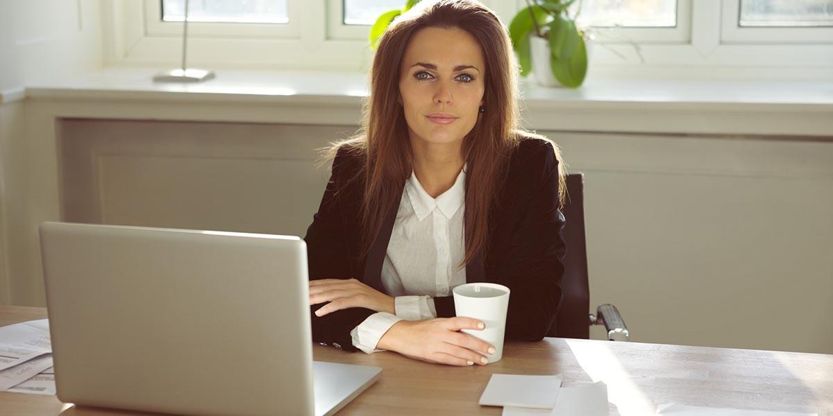 Gerente mujer mirando a la cámara mientras señala ideas sobre cómo adaptar el negocio en el laptop