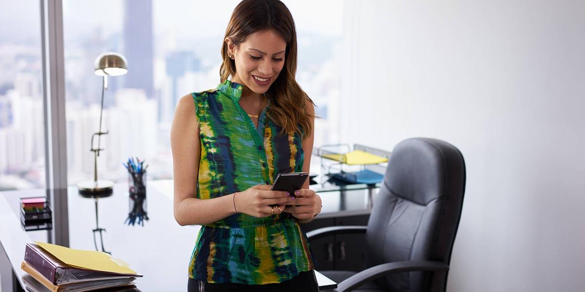 Joven empresaria en la oficina y a consultar en smartphone la Prórroga de los ERTE
