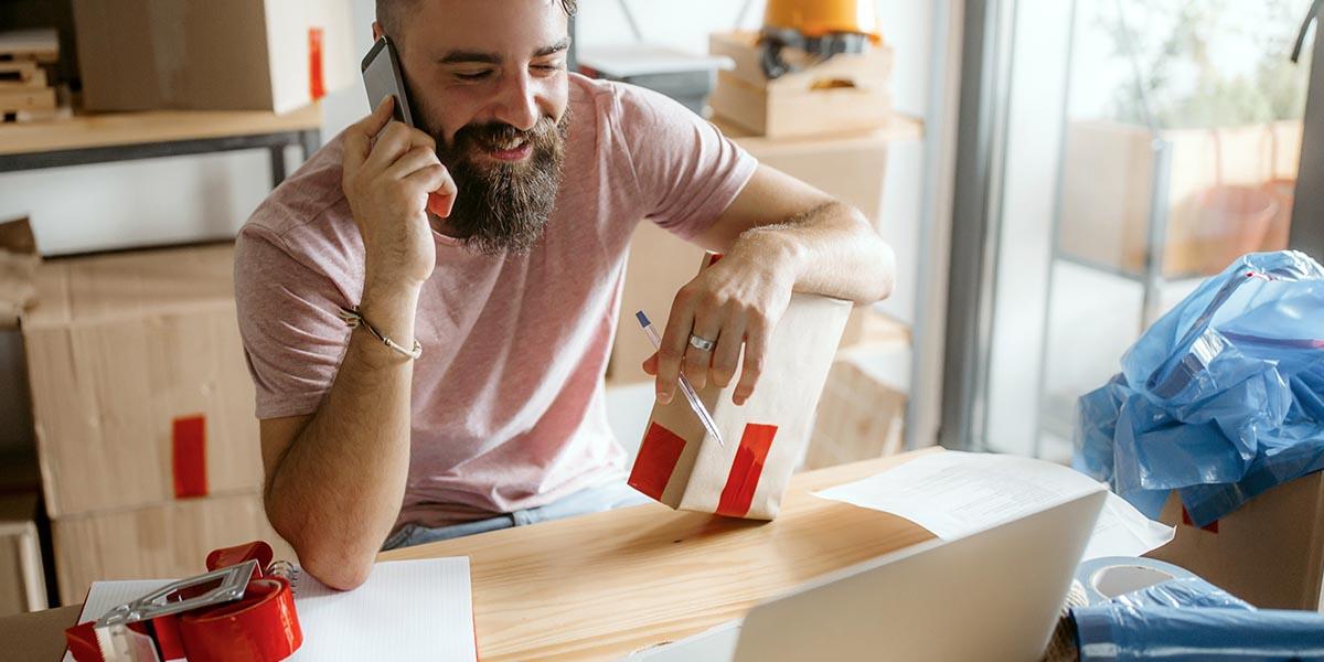 Hombre emprendedor impulsando su negocio a través de una tienda online mientras habla por teléfono