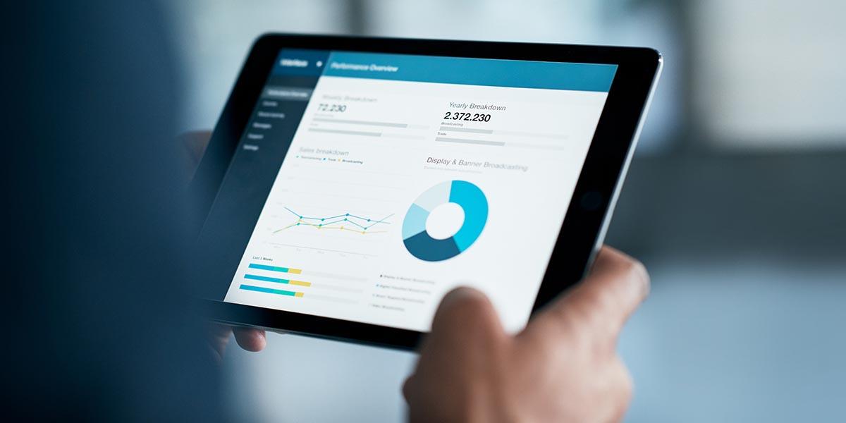 Mão de um homem a segurar num tablet com os dashboards de uma empresa data-driven