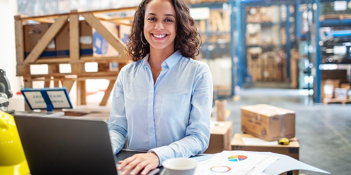 Mujer de negocios mirando la foto mientras realiza la gestión de activos fijos en el almacén de la empresa