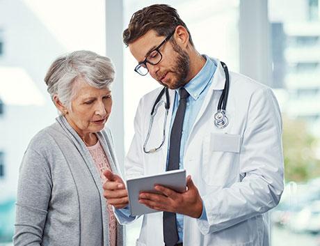 Médico ensenãndo los resultados médicos a su paciente en una tablet con Software de Gestión PHC CS