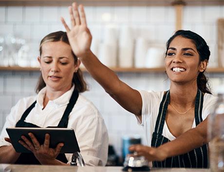 dos camareras saludando a un cliente en el restaurante