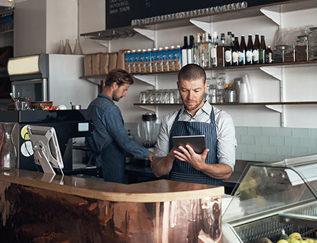 dos camareros en la barra del bar contando el dinero del día
