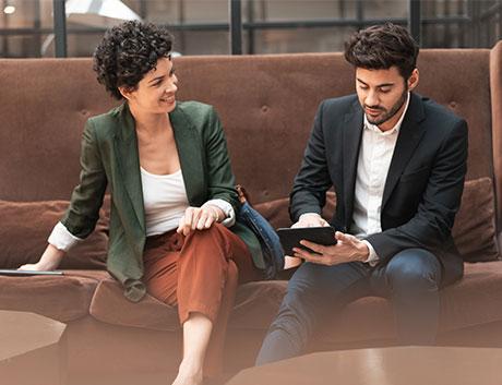 Dos compañeros de trabajo viendo las ventas del mes a través de una tablet con Software de Gestión para CRM