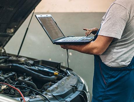 mecánico en el taller revisando un coche con ayuda del software de gestion para flotas