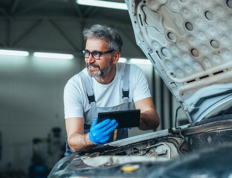 mecánico reparando un coche con la ayuda de un tablet con software de gestion para flotas