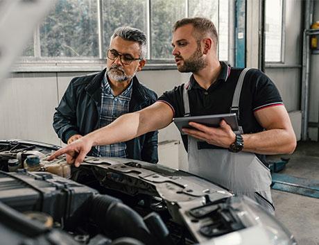 el cliente y el mecánico explicándole los arreglos del coche
