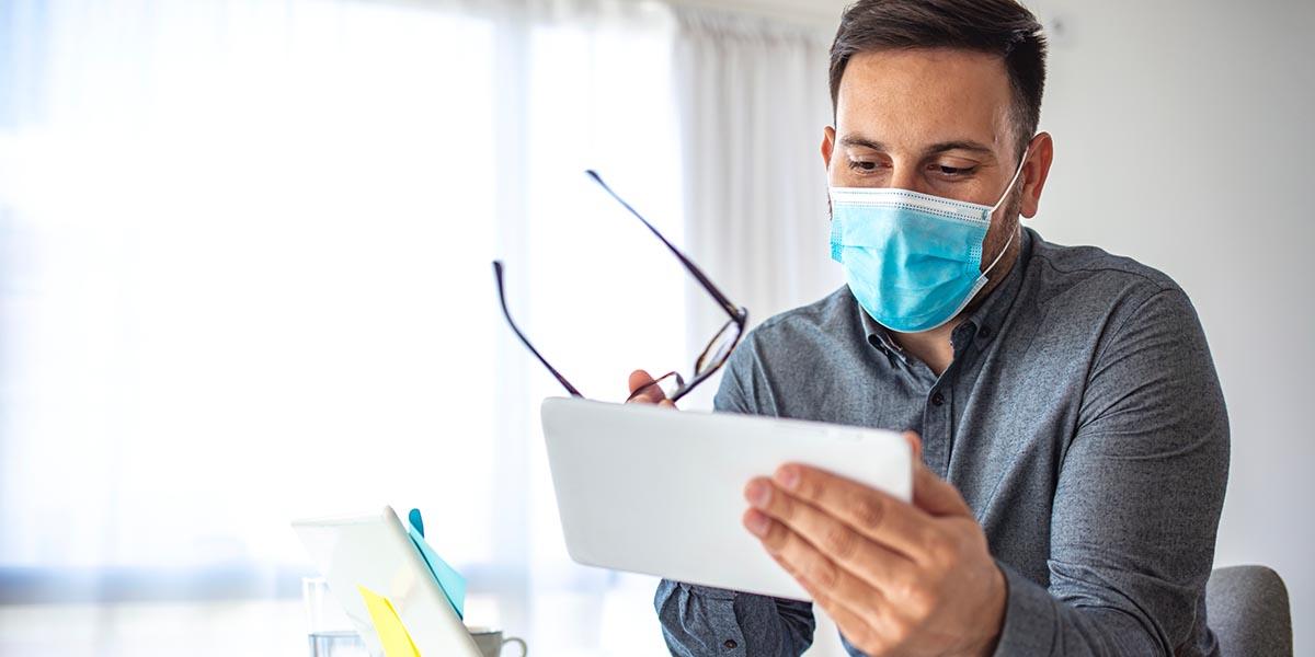 hombre con máscara consultando en el tablet las medidas Covid de apoyo a las empresas