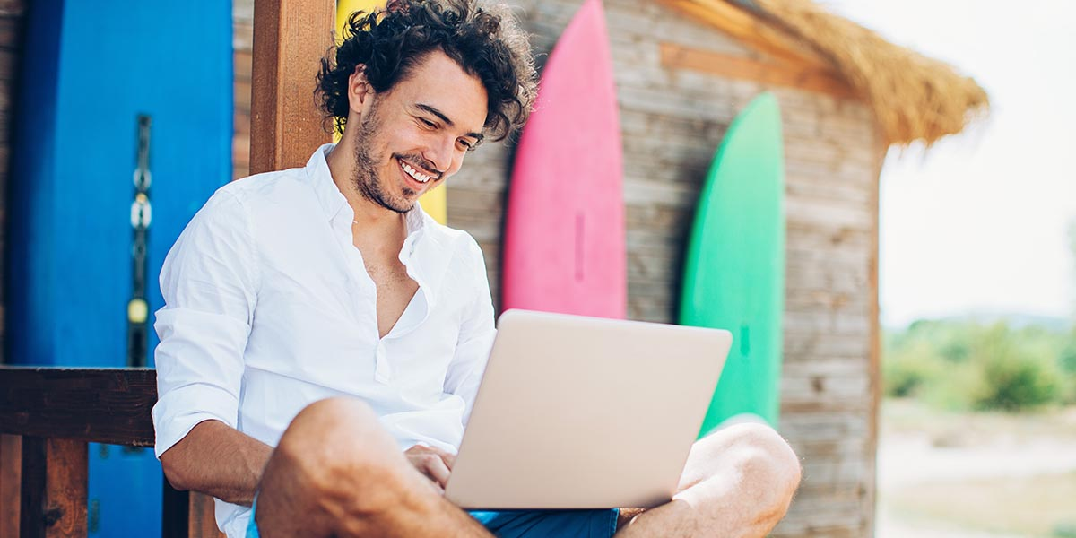 joven empresario sentado en la playa consultando el modelo 365